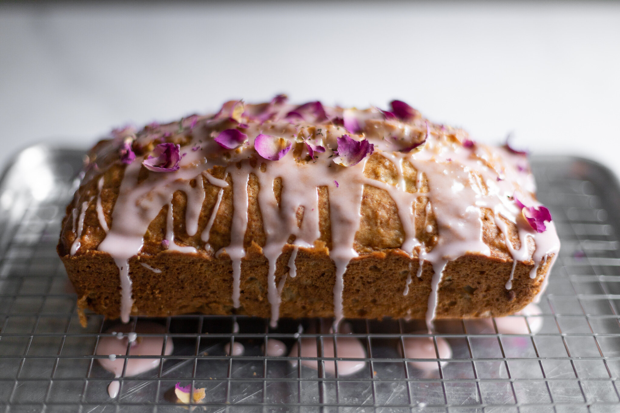 a rectangular quince loaf cake with light pink icing dripping down the sides and rose petals on top, from a 45 degree angle