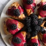 blackberry scones topped with magenta icing and fresh blueberries