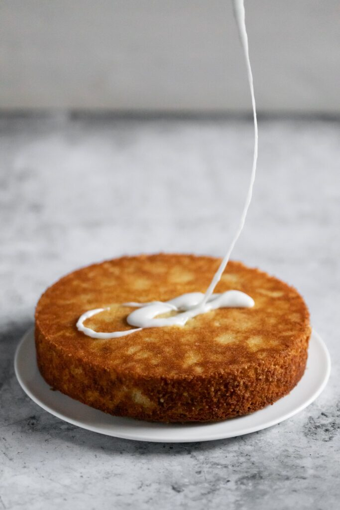 icing being drizzled on a cake