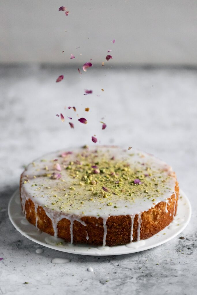 dried rose petals being sprinkled on a cake