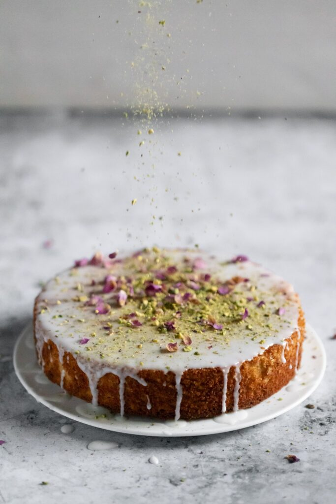 pistachios being sprinkled on an iced cake
