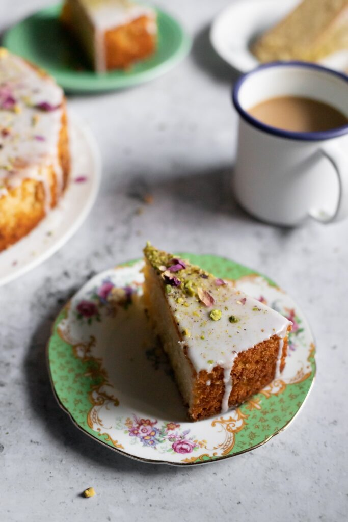 a slice of Persian love cake with coffee and more slices in the background