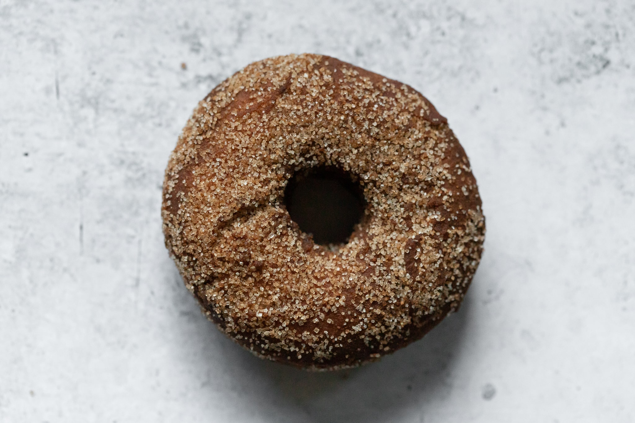 a cinnamon sugar old fashioned donut photographed from above